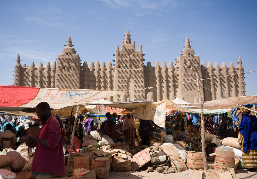 A busy local market sprawls in front of the enormous mud mosque in Djenne, Mali