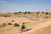 A boy on a bicycle rides past roadside brickworks using mud from the river outside Djenne in Mali