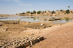 Large mud bricks dry in the sun next to a fan of pirogue boats on the outskirts of Djenne in Mali
