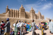 Market stalls set up against the wall of the mosque in Djenne Mali