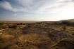 A stark, burned landscape of bare sandstone and dry scrub forms the edge of the Bandiagara escarpment in Mali.